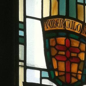 Stained glass window with double cross and the word Tuberculosis
