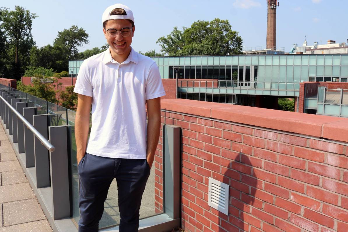 Alberto laughs while standing on rooftop with brick backdrop