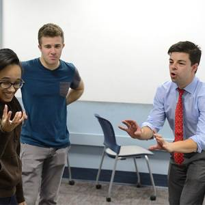 Three students participate in improv comedy exercise