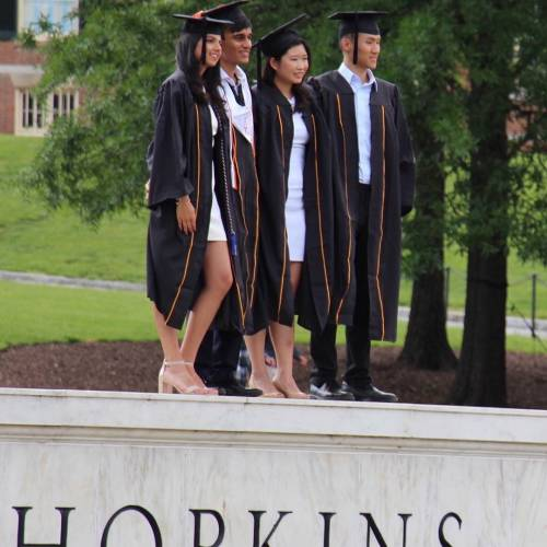 Four graduates stand on top of the Hopkins sign