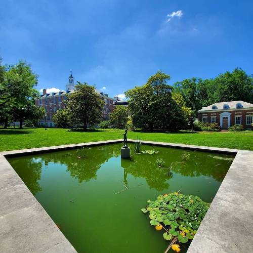 A green fountain against the backdrop of a campus quad