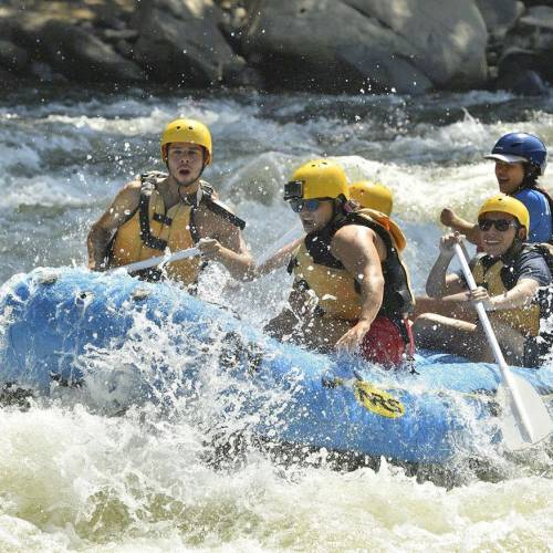 Five people in a whitewater raft in rapids