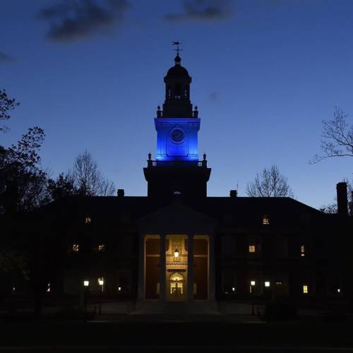 Campus building at dusk illuminated by blue lights