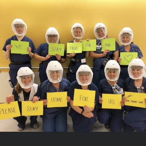 Nurses in PPE with signs reading: We stay here for you; please stay home for us