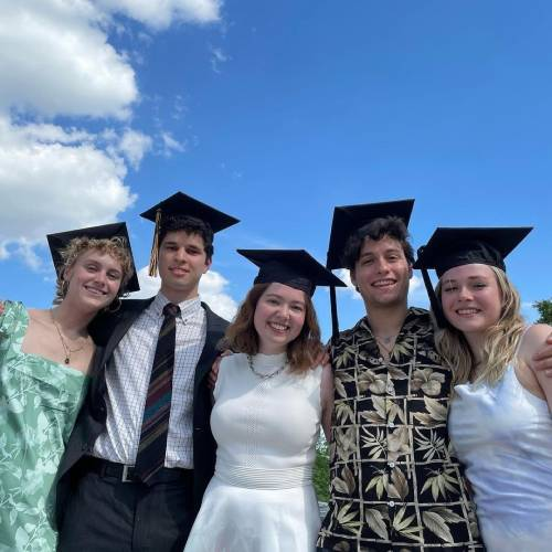 Five individuals in graduation caps pose for a photo